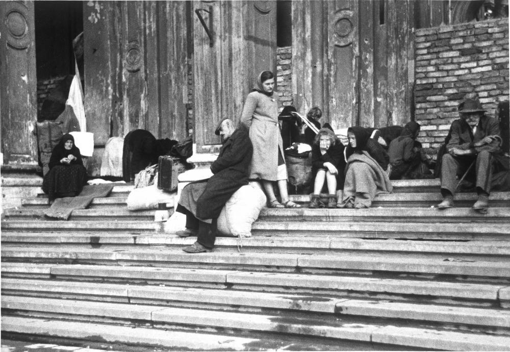 Der Titel dieses Bildes bezeichnet diese Menschen als Wohnungslose. Durch Kriegszerstörungen und Flucht hatten viele ihre Unterkunft verloren und hofften nun, Quartiere zugewiesen zu bekommen.