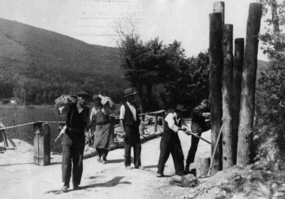 """Früh begannen vor Ort stationierte Besatzungstruppen mit dem Abbau militärischer Befestigungen. Dabei wurden oft ehemalige NSDAP-Mitglieder angehalten, diese Reste des behaupteten """"Endkampfs"""" zu beseitigen. Wer hier bei der Demontage von Panzersperren aus Baumstämmen abgebildet wurde, ist jedoch nicht bekannt."""